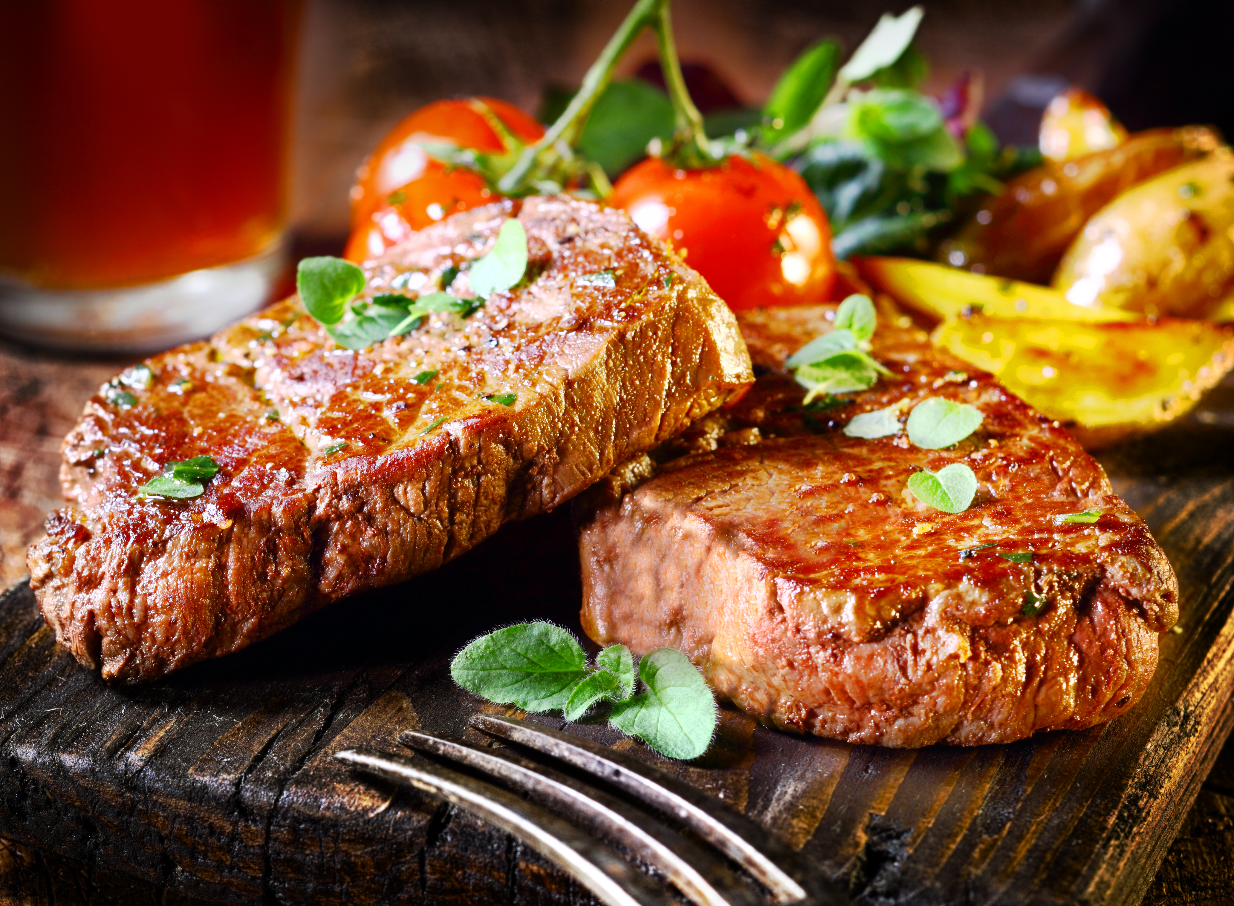 Steak served with roasted tomatoes and potatoes