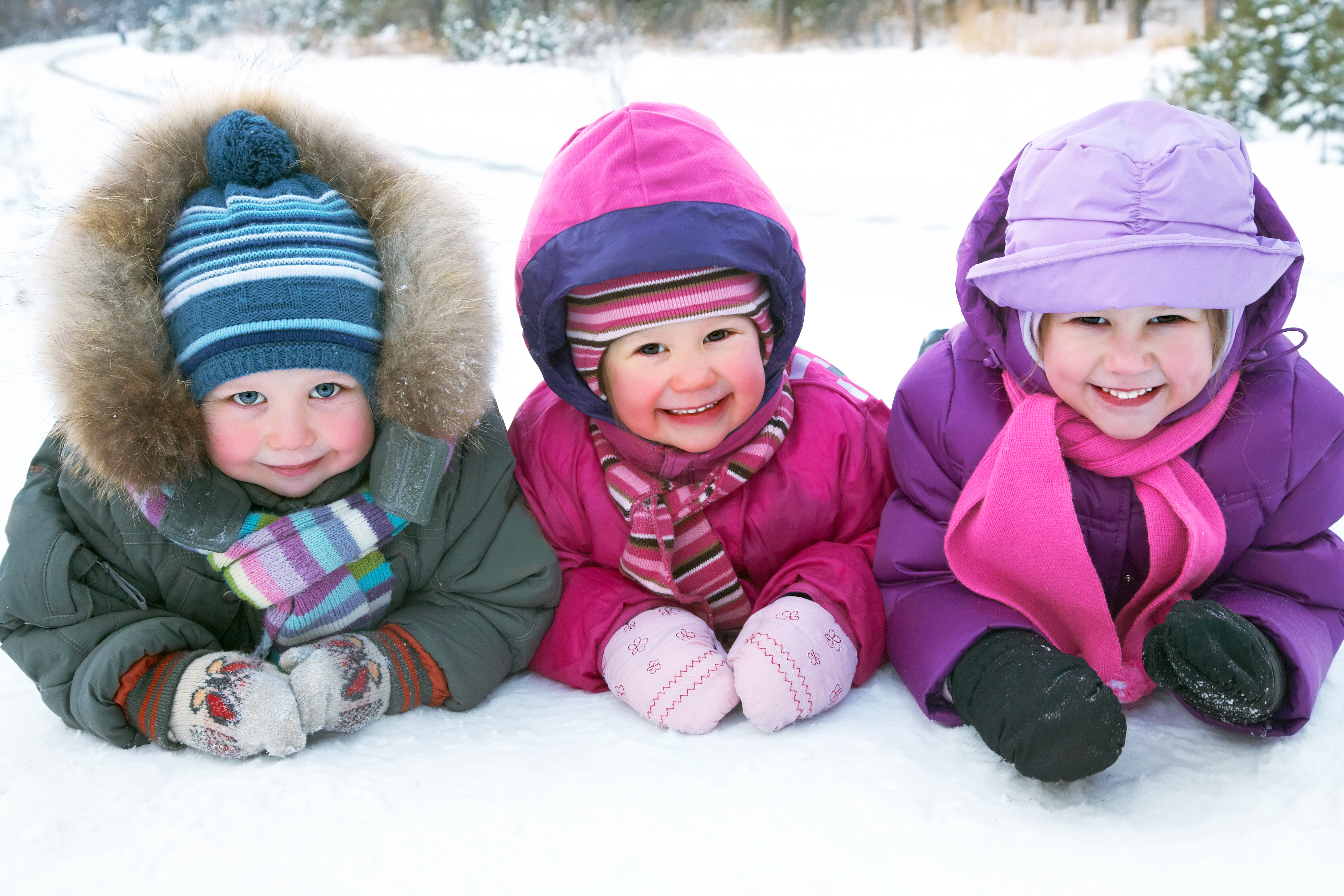 Kids laying in snow smiling