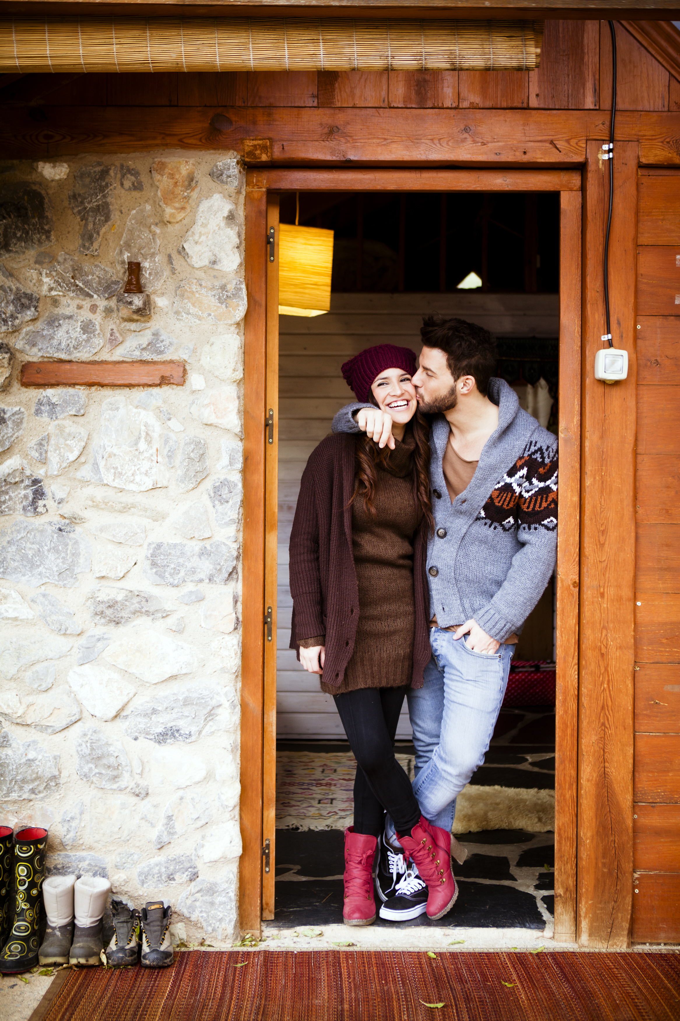 Couple standing in the cabin door with the guy kissing the girl on cheek