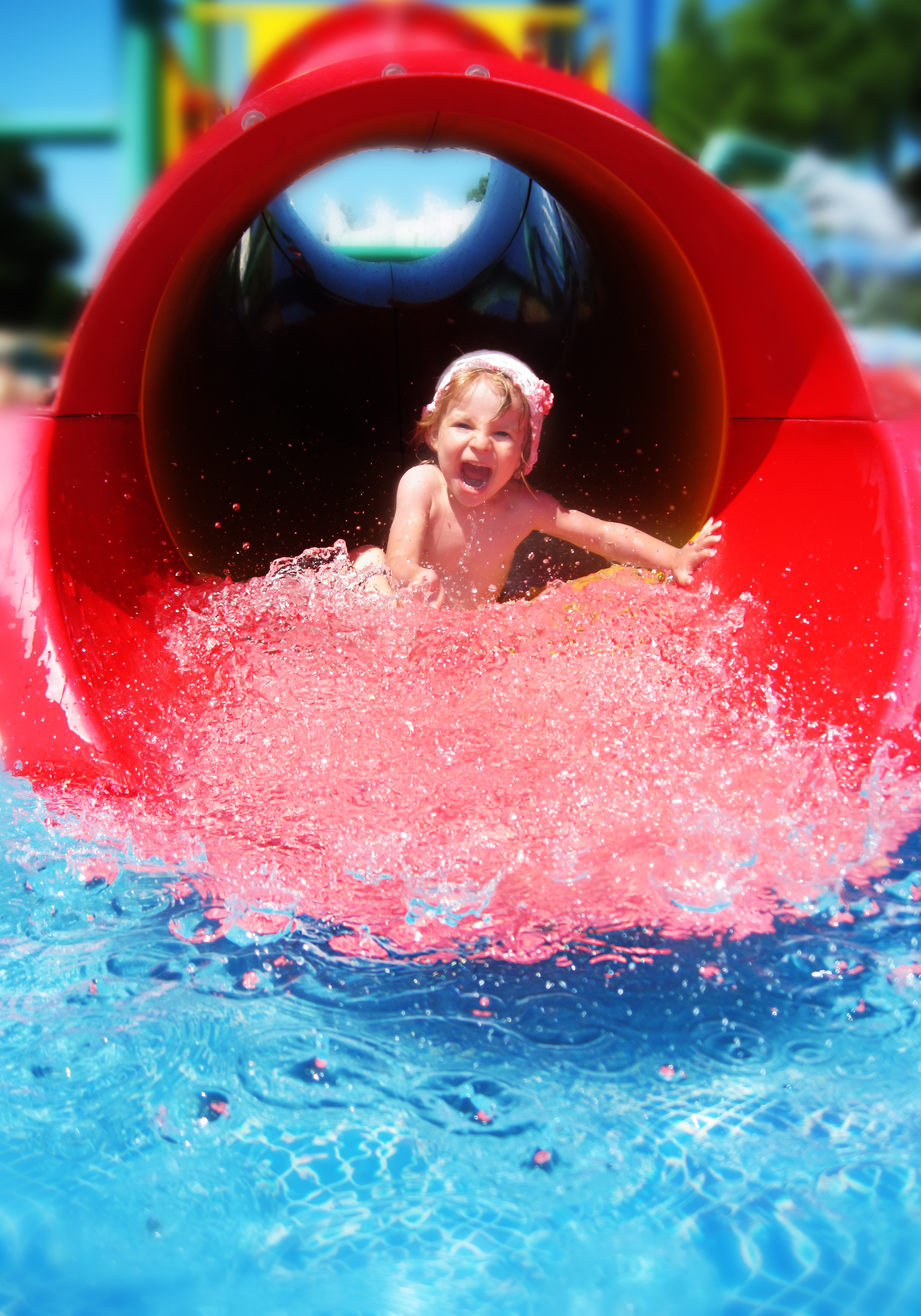 Happy girl coming down the red water slide