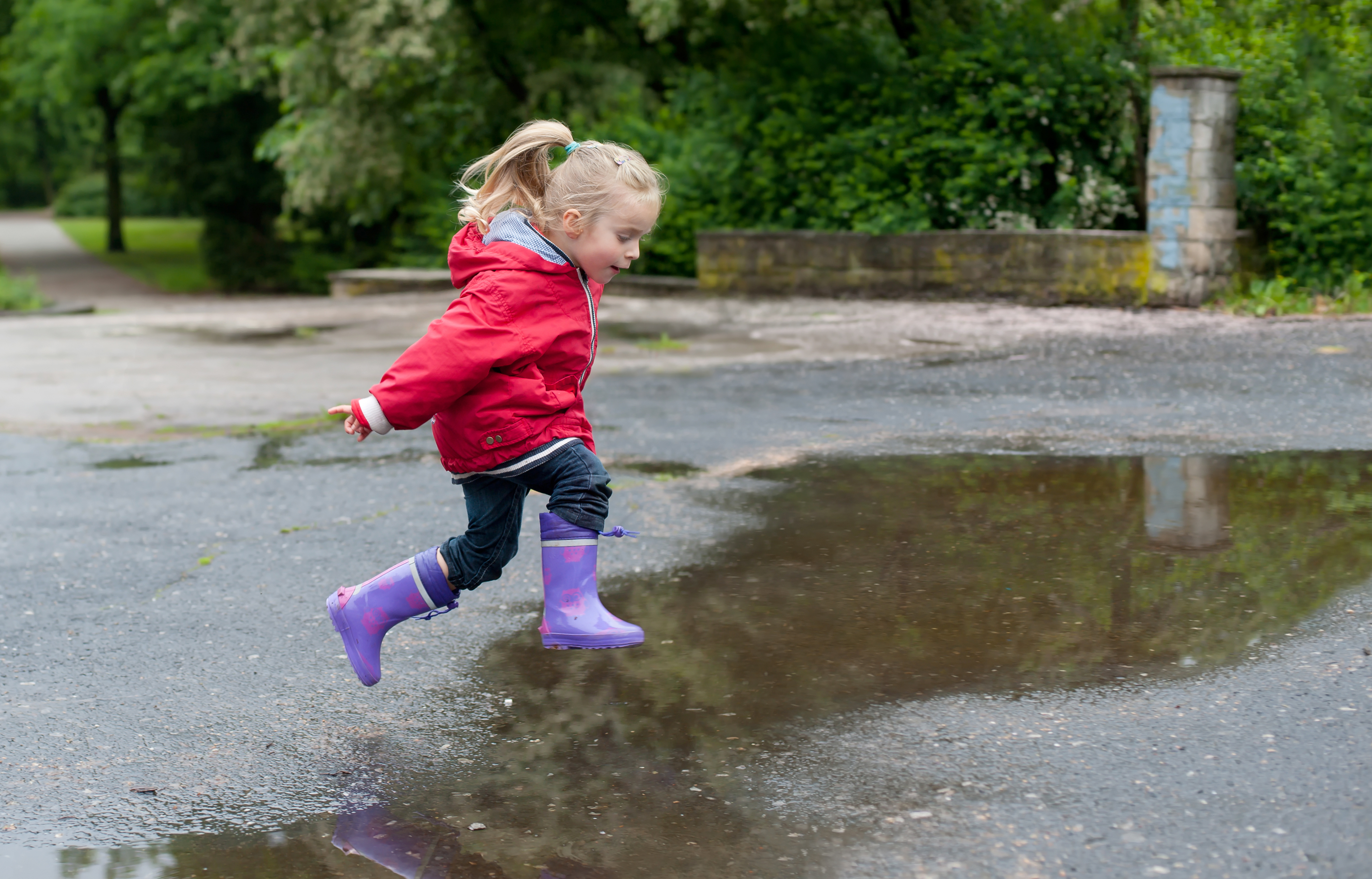Kid jumping in the puddle in the rain