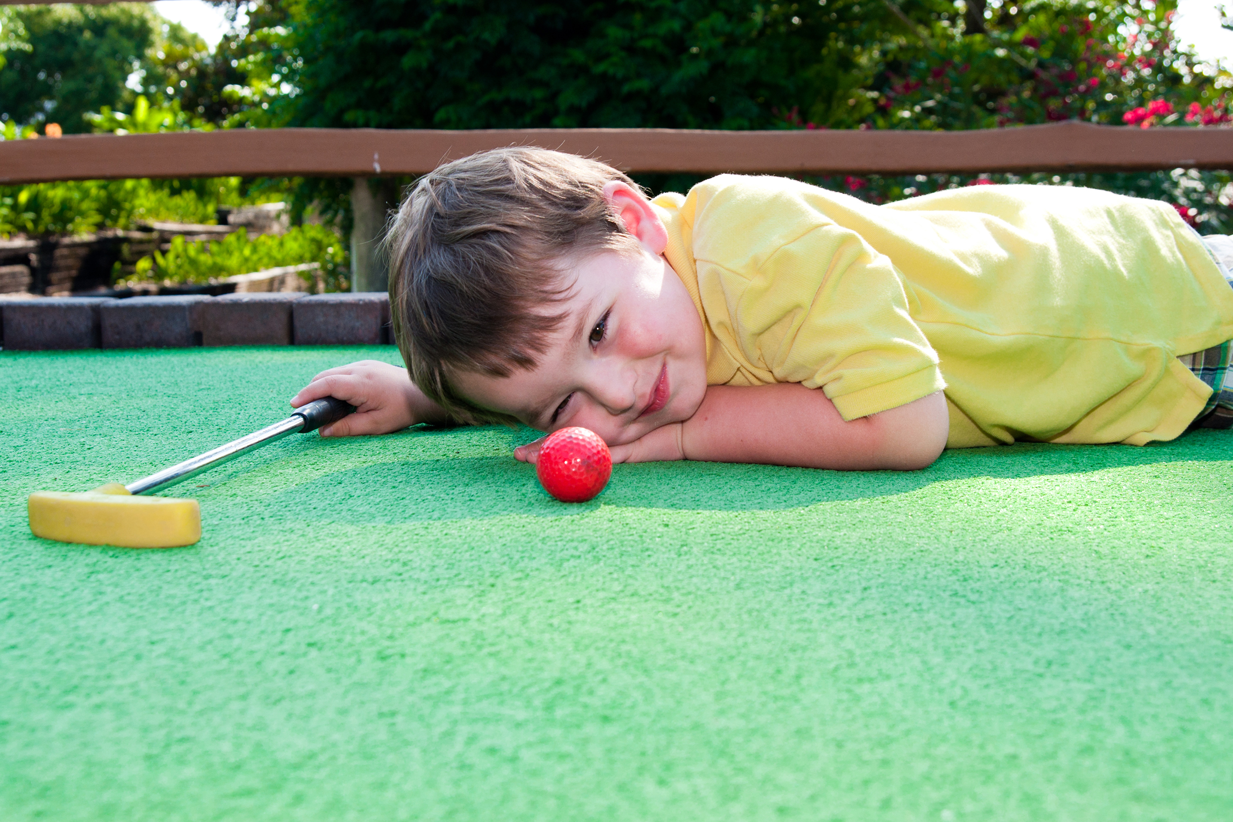 Kid laying on the mini golf course